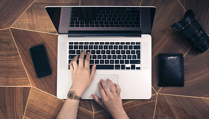 Hands typing and using scrollpad on a laptop