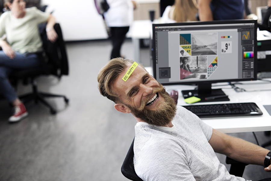 happy man in office with sticker that says be happy on forehead