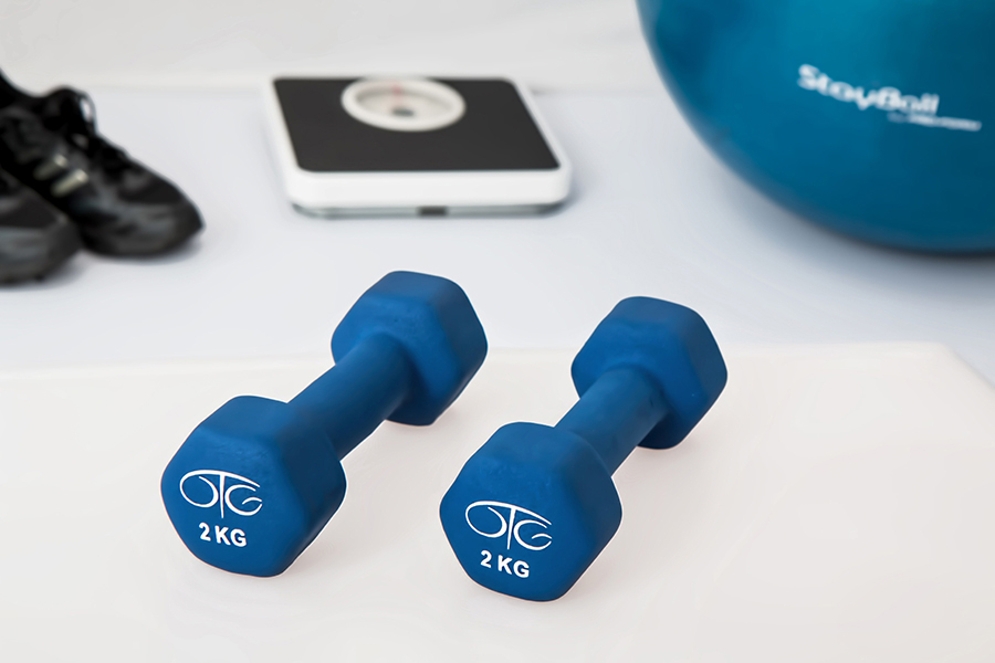two blue dumbbells, a scale, trainers, and yoga ball
