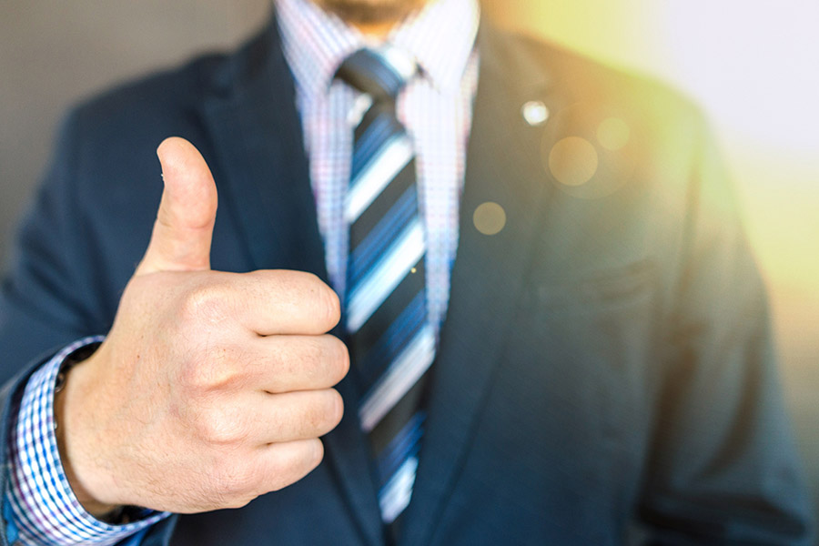 man in suit doing a thumbs up