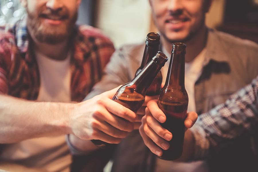 Men with bottles of beer saying cheers