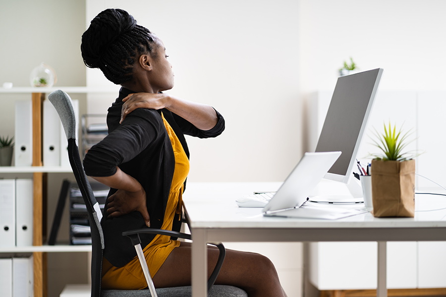 Woman rubbing her back and shoulders at her desk